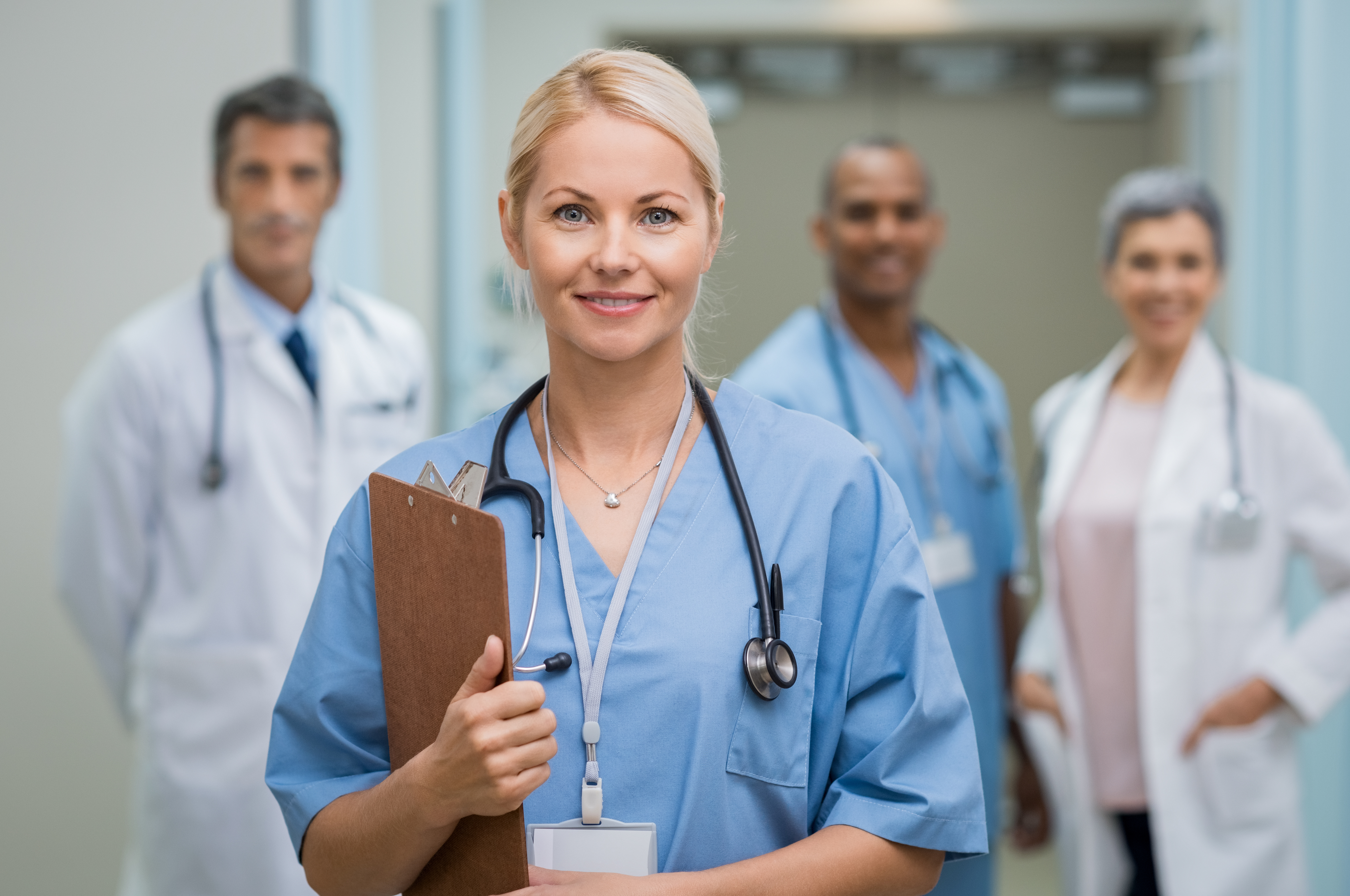 Nurse stands in forefront with doctors in the background, illustrating nurse leadership issues and burnout among nurses | healthcare news | Primaris