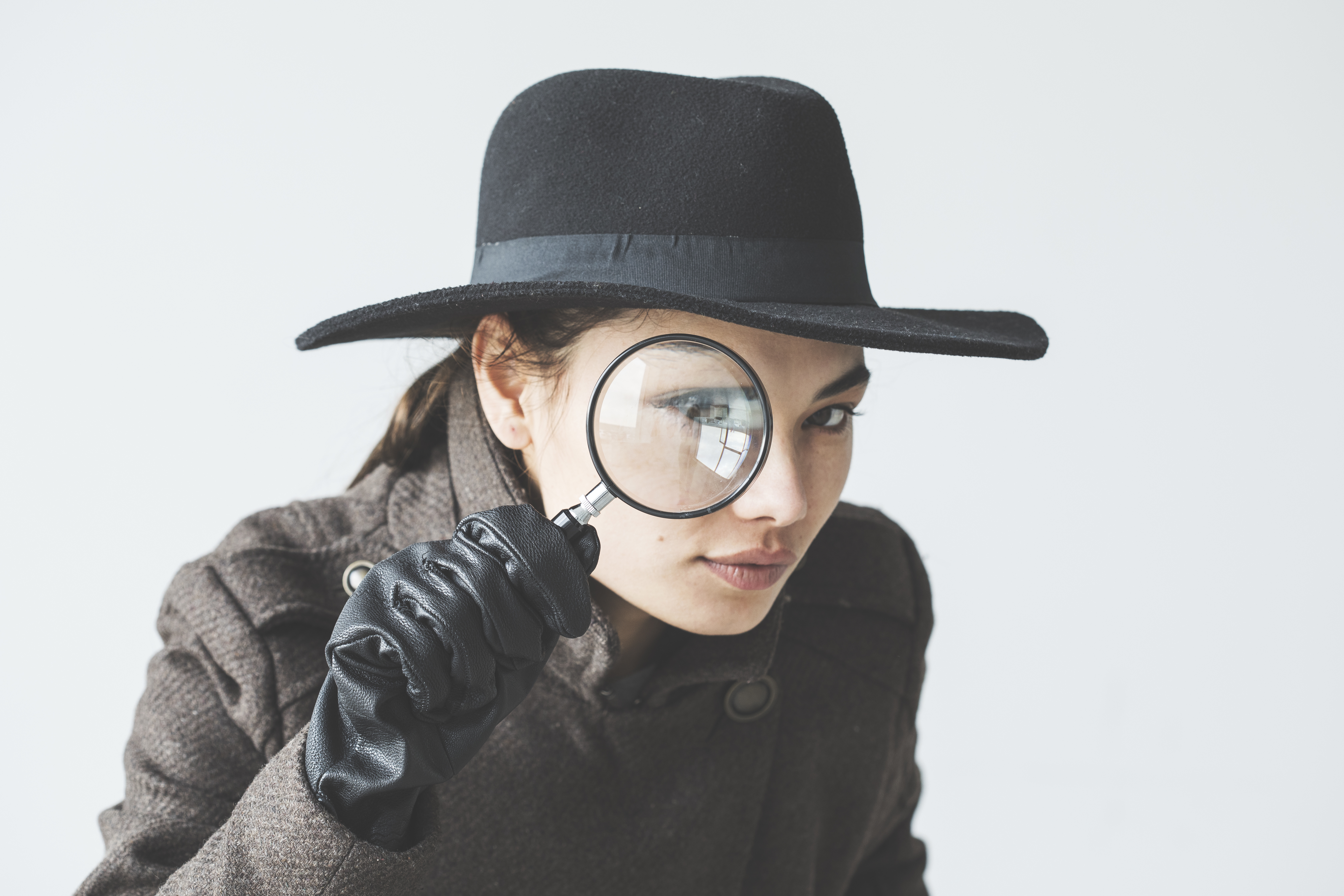 Female detective uses magnifying glass to illustrate searching for missing healthcare data | Registry Abstraction | Primaris