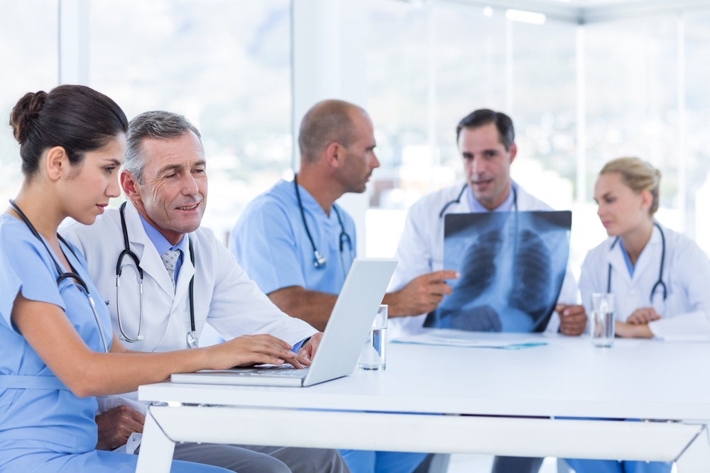 Doctors using computer whiles theirs colleagues looking at Xray in medical office.jpeg