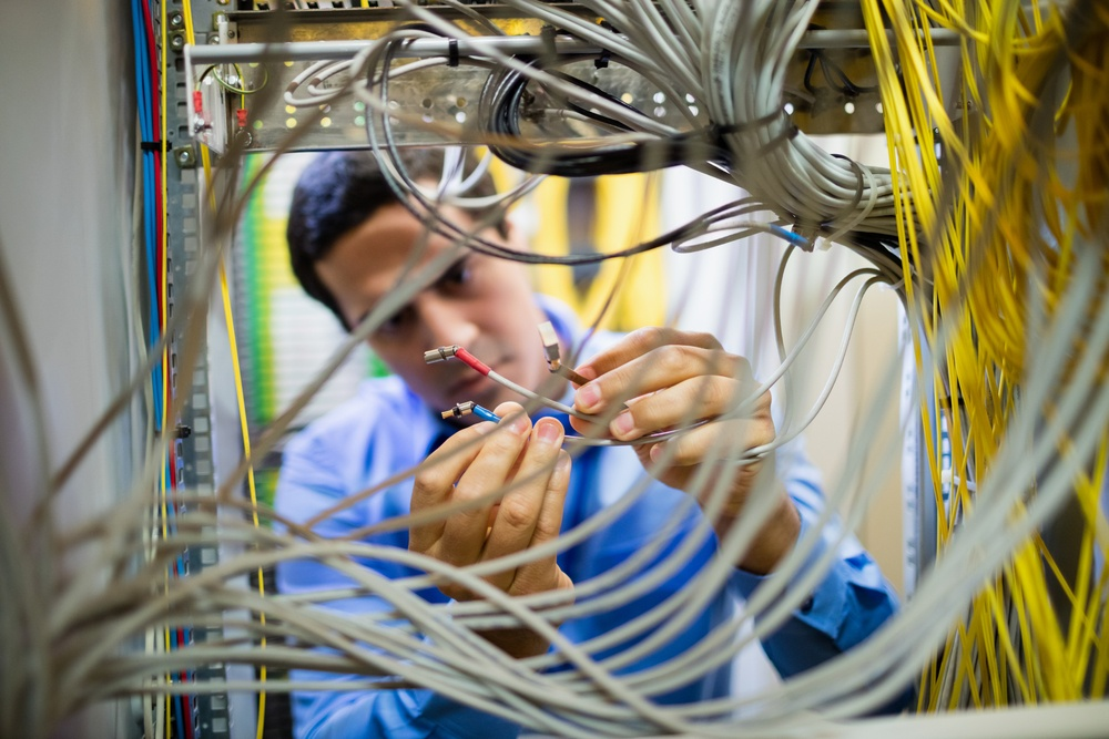Attentive technician fixing cable in server room