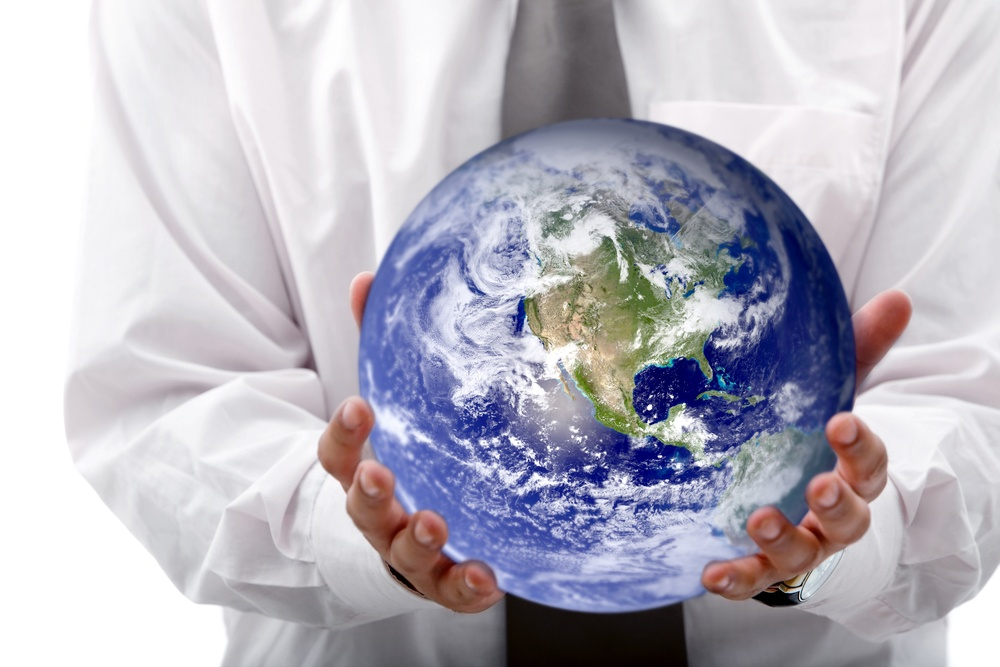 Business woman holding globe isolated over a white background.jpeg