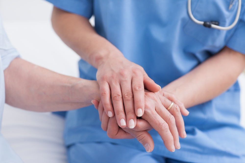 Close up of a nurse touching hand of a patient in hospital ward, illustrating a hospital's patient safety culture.