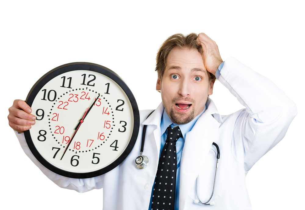 Closeup portrait of an overwhelmed with busy schedule, unhappy male health care professional doctor or nurse holding big clock running out of time isolated on white background-2