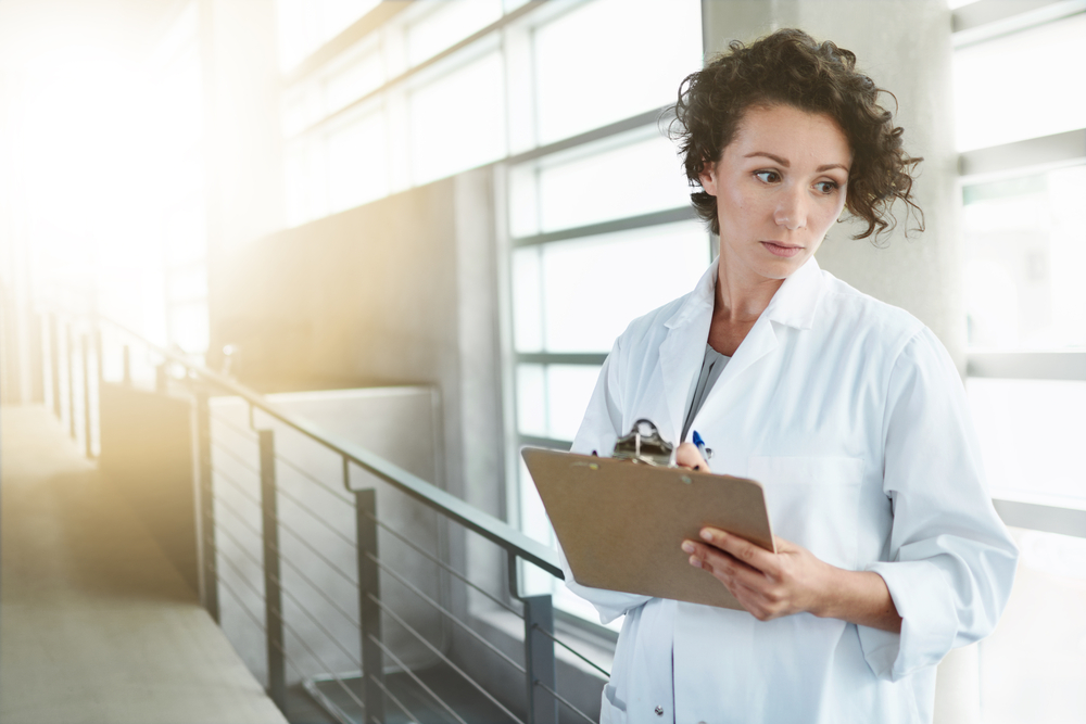 Portrait of a serious female doctor holding her patient chart in bright modern hospital