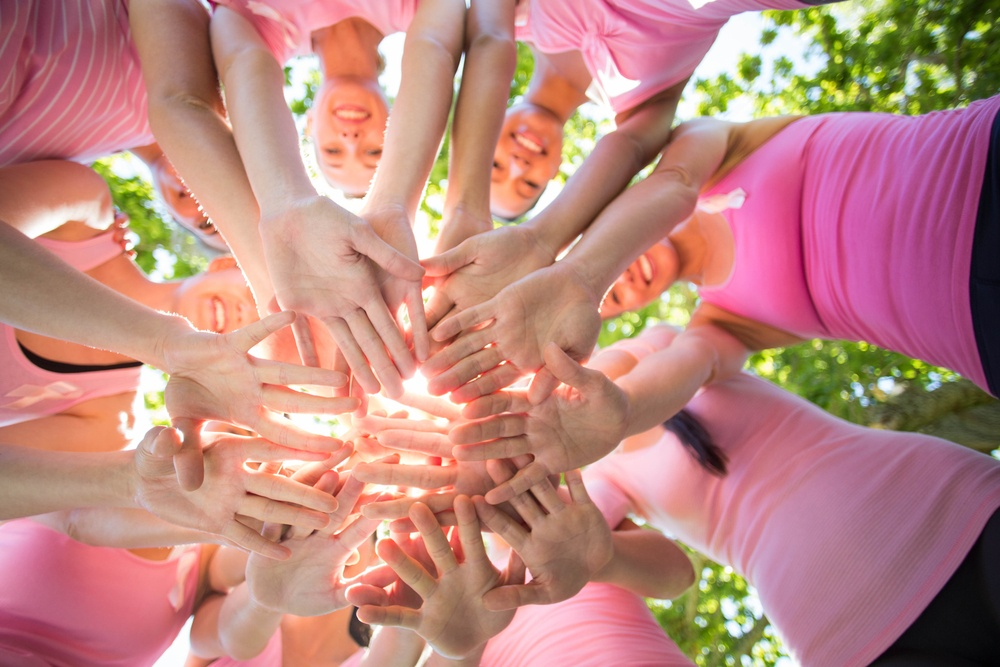 Smiling women organizing event for breast cancer awareness on a sunny day. They are all wearing pink shirts.