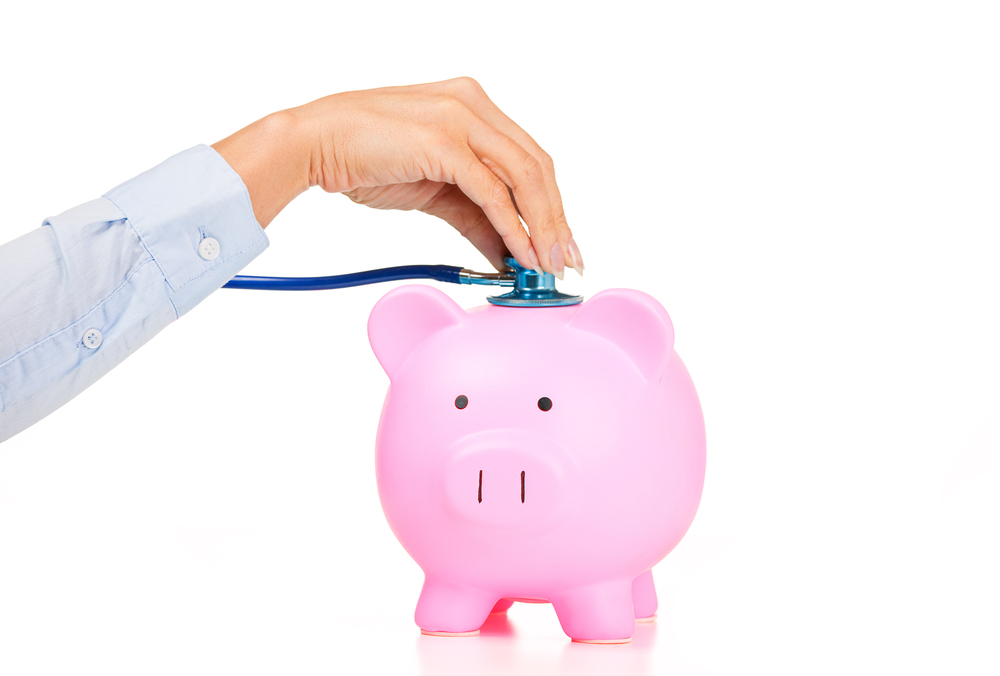 Woman hand stethoscope pink piggy bank. Financial system checkup   healthcare news   Primaris