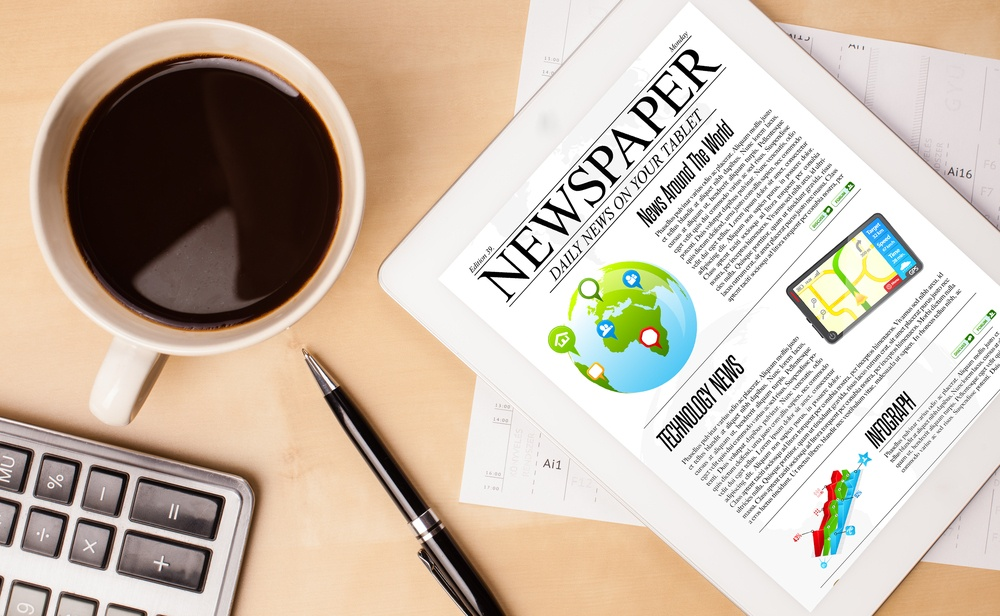 Image of desk surface with cofee cup, keyboard, newspaper to illustrate weekly roundup of health news: megamergers, MACRA, WebMD briefs, Don Berwick on value-based care, more.