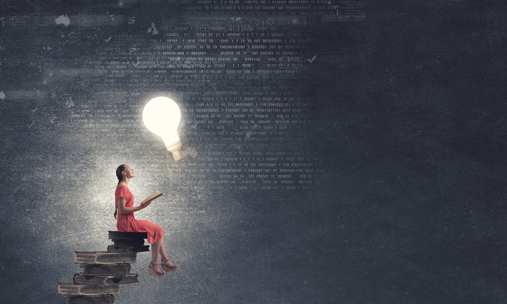 Woman reading with giant, hovering light bulb portraying important thought, education.