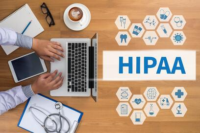 A physician works at her laptop, surrounded by medical symbols and the HIPAA acronym | healthcare consulting | Primaris